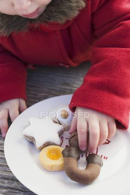 Recadrée vue de fille prenant le biscuit de Noël de plaque — Photo de stock