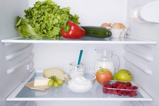 An open fridge with various types of fresh produce — Stock Photo