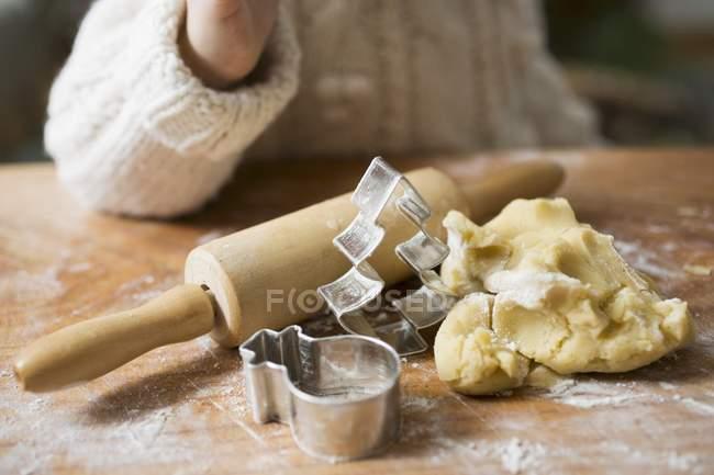 Cortada a visão da criança perto de massa de biscoito, cortadores e rolling pin — Fotografia de Stock