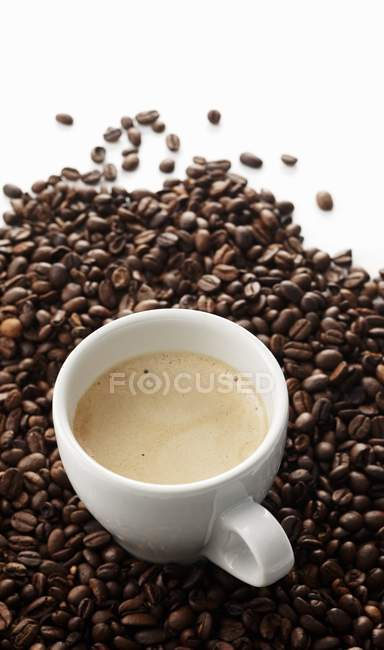 Espresso in cup on coffee beans — Stock Photo