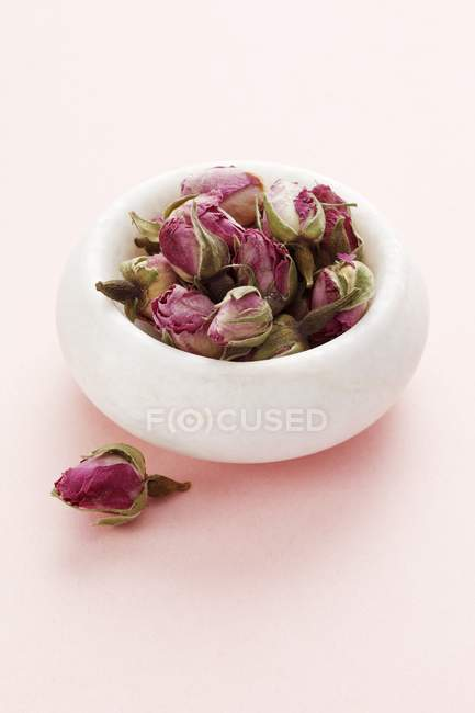 Closeup view of a white bowl of rose buds — Stock Photo