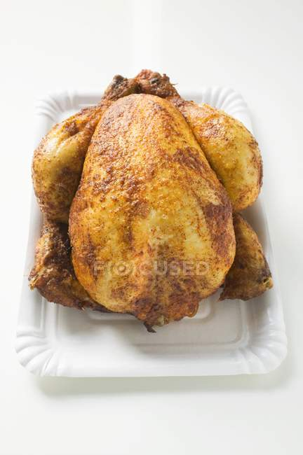 Whole roasted chicken on paper plate — Stock Photo