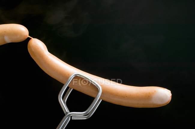 Щипці проведення сосиски — стокове фото