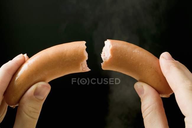 Hands holding a halved frankfurter — Stock Photo