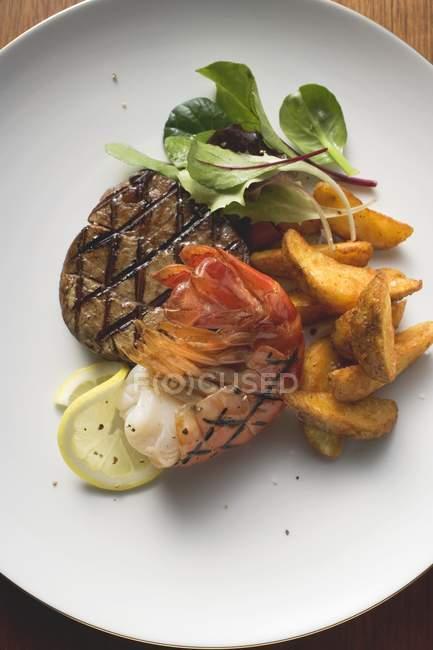Filete de ternera y gambas con cuñas de patata - foto de stock