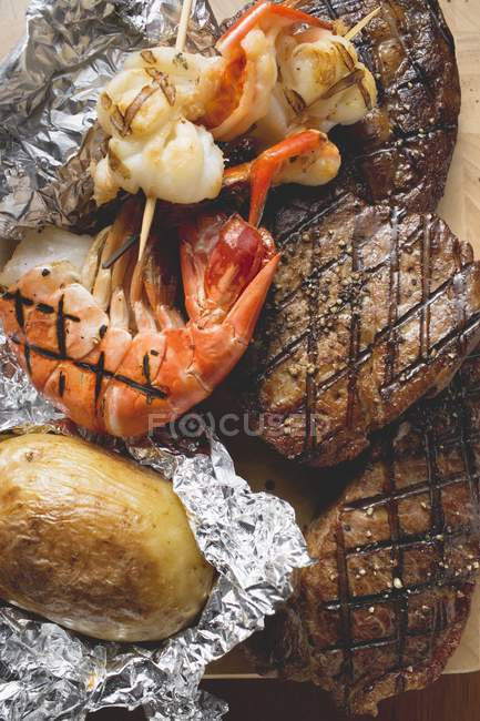 Beef fillet and prawn with baked potato — Stock Photo