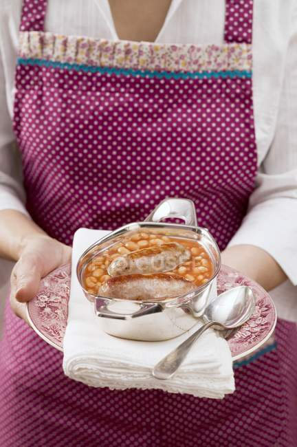 Donna che serve di fagioli con salsicce — Foto stock