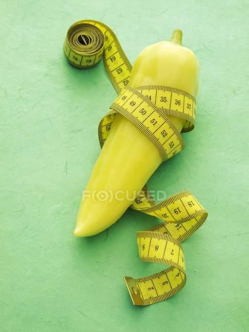 Pimienta puntiaguda con cinta métrica - foto de stock
