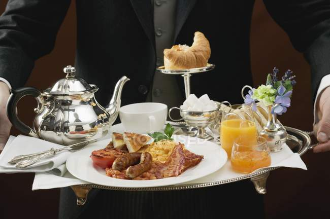Butler serving English breakfast on tray — Stock Photo