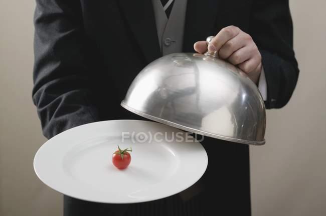 Дворецкий подает помидор черри на тарелке с купольной крышкой, в середине — стоковое фото