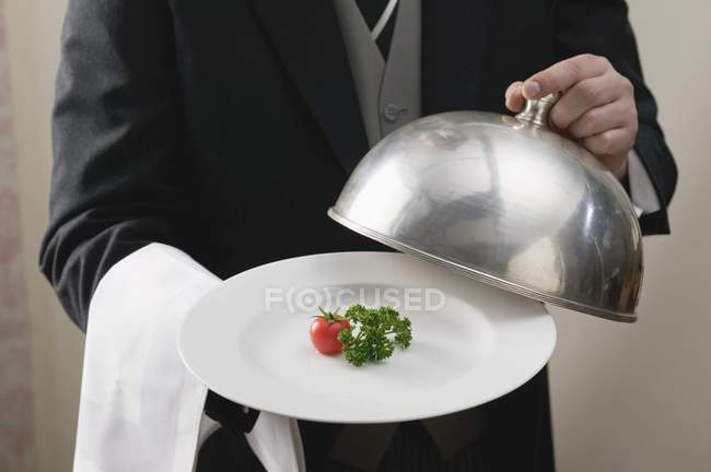 Butler serving tomato and parsley on plate with dome cover in hands, midsection — Stock Photo