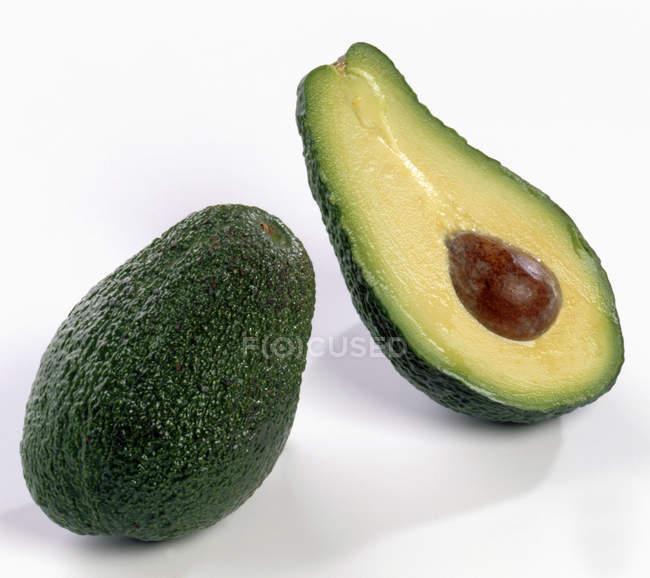Целом и половина авокадо — стоковое фото