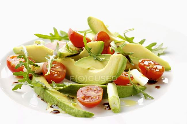 Avocado salad with cherry tomatoes on white plate — Stock Photo