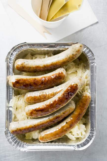 Sausages with sauerkraut in aluminium container — Stock Photo