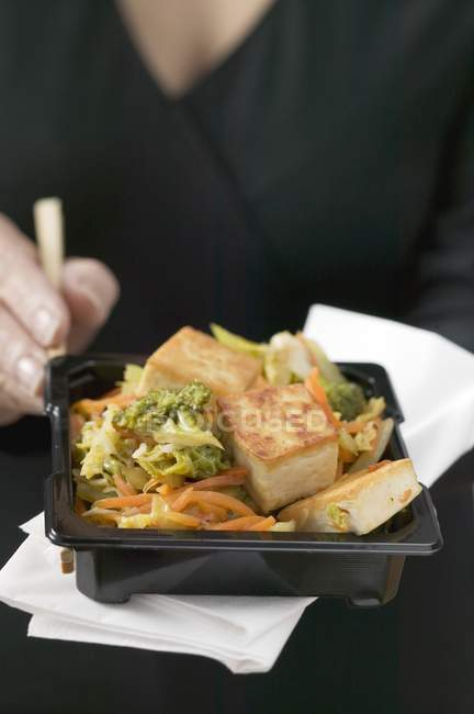 Woman holding tofu with vegetables — Stock Photo