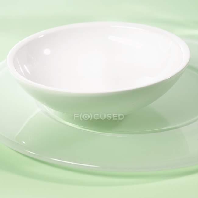 Vista de cerca del tazón de fuente blanco en un plato de servicio - foto de stock