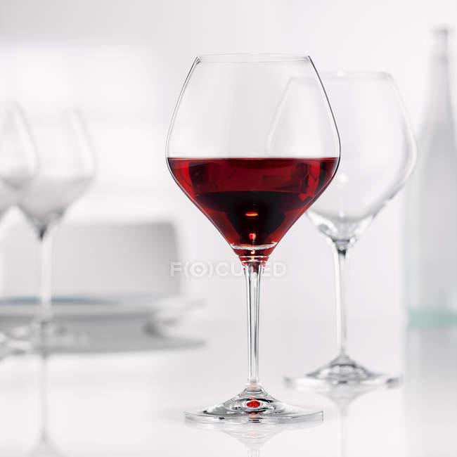 Burgunderglas mit leeren Gläser — Stockfoto