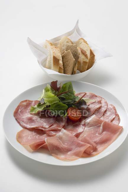 Raw ham and salami on plate — Stock Photo