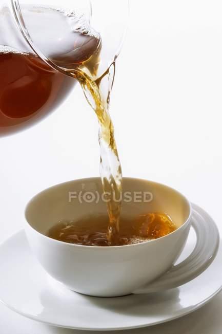 Pouring tea into a teacup — Stock Photo