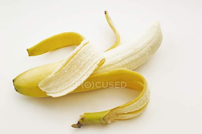 Один частково очищені банан — стокове фото