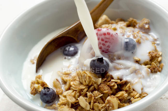 Pouring milk over crunchy muesli — Stock Photo