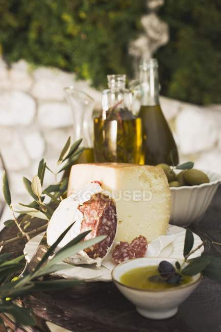 Cheese with salami and olives on table — Stock Photo