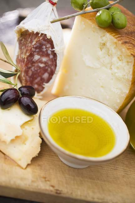 Salami with olives and Parmesan on wooden surface — Stock Photo
