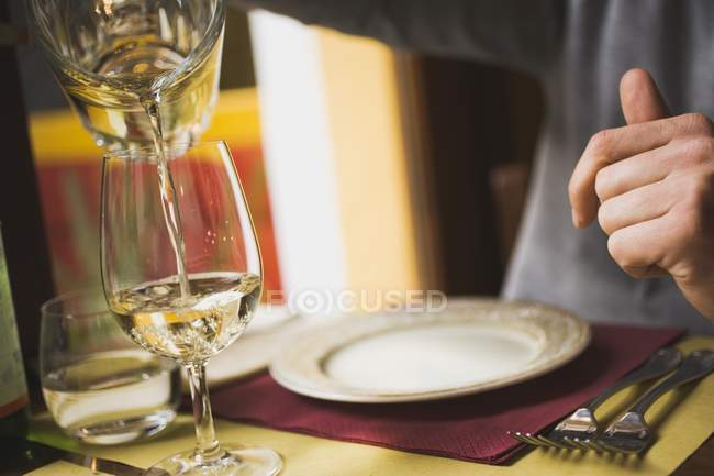 Pouring white wine from carafe into glass — Stock Photo