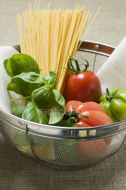 Tomatoe and spaghetti in sieve — Stock Photo