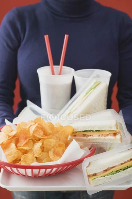 Mujer sosteniendo sándwiches, cola y patatas fritas en bandeja - foto de stock