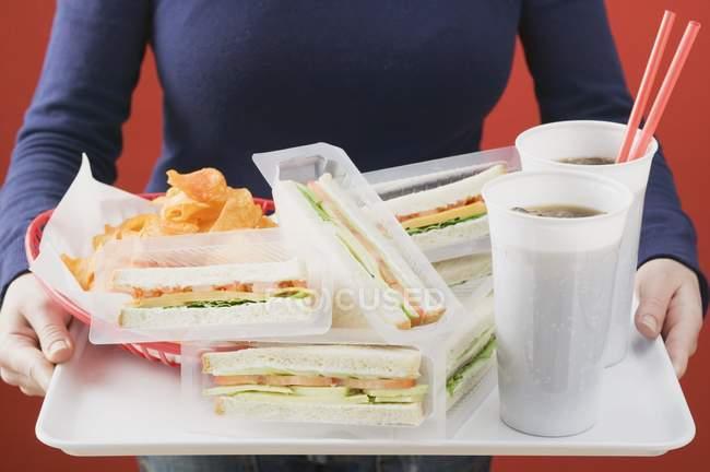 Vista de cerca de la mujer sosteniendo sándwiches con cola y patatas fritas en la bandeja - foto de stock