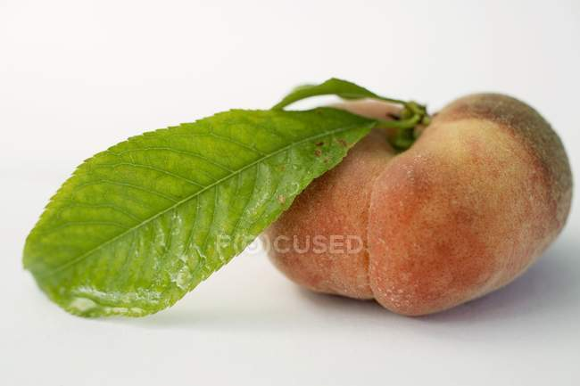 Melocotón maduro con hoja - foto de stock