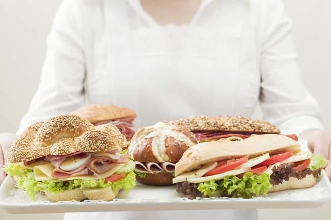 Жінка тримає підношення Асорті бутерброди — стокове фото