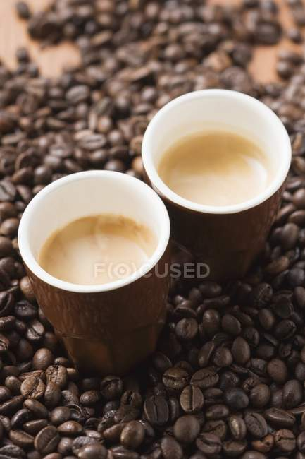 Cups of espresso on coffee beans — Stock Photo