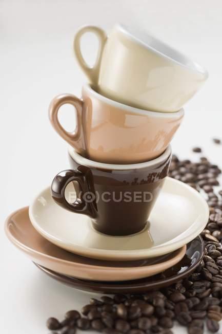 Tazas de café expreso apiladas y granos de café - foto de stock
