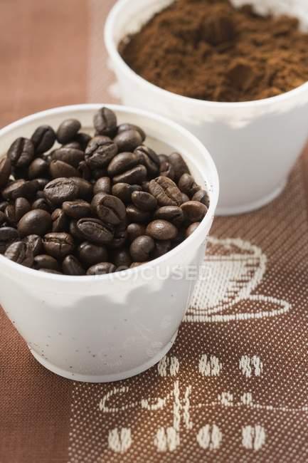 Кофейные зерна и порошок в стаканах — стоковое фото