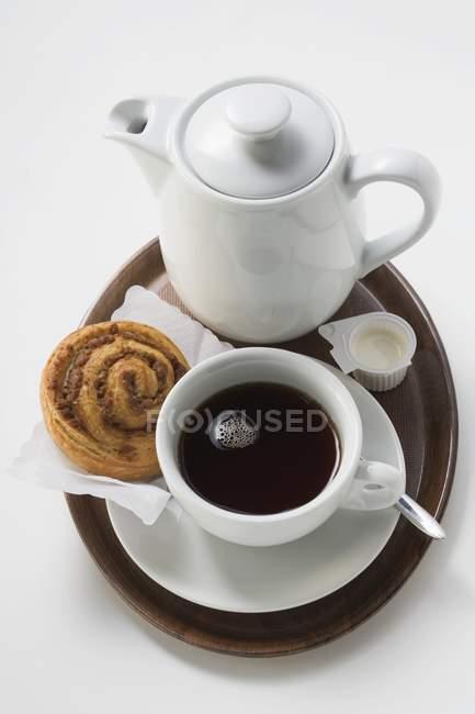 Tazza di caffè con panino alla cannella — Foto stock