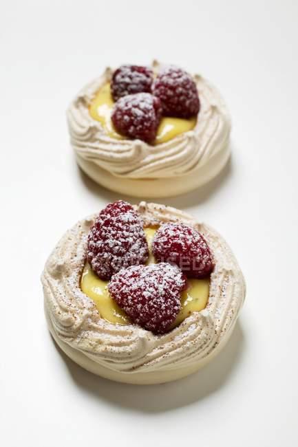 Merengues con crema de vainilla y frambuesas - foto de stock