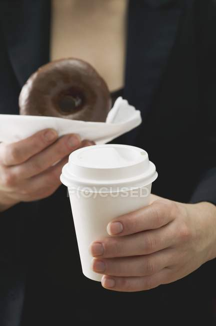 Woman holding doughnut and coffee cup — Stock Photo