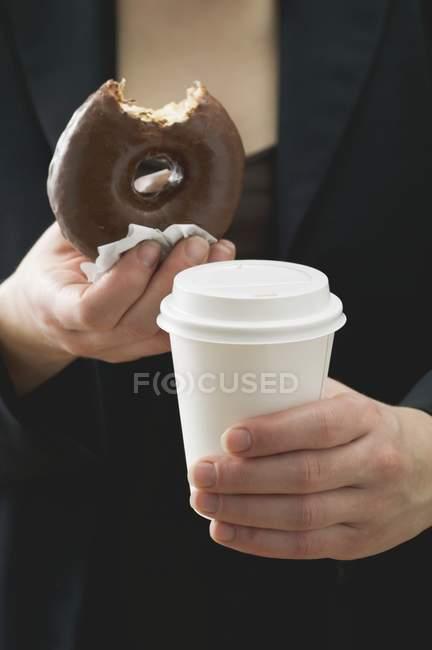 Mujer sosteniendo rosquilla y taza de café - foto de stock