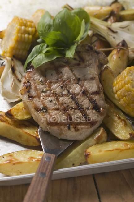 Pork chop on roasted potatoes — Stock Photo