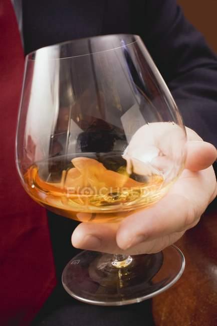 Руки, що тримає склянки коньяку — стокове фото