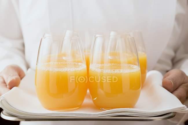 Camareira servindo suco de laranja em óculos — Fotografia de Stock