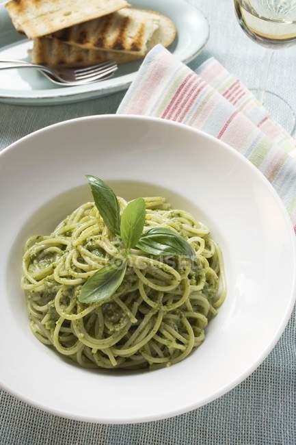 Макароны спагетти с соусом песто и базиликом — стоковое фото