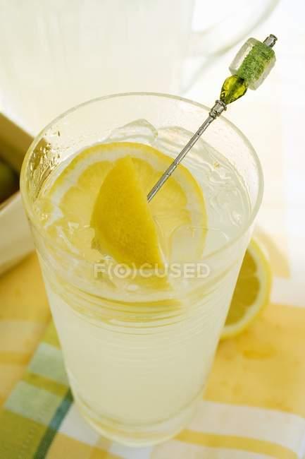 Лимонад в стакане со свежими лимонами — стоковое фото