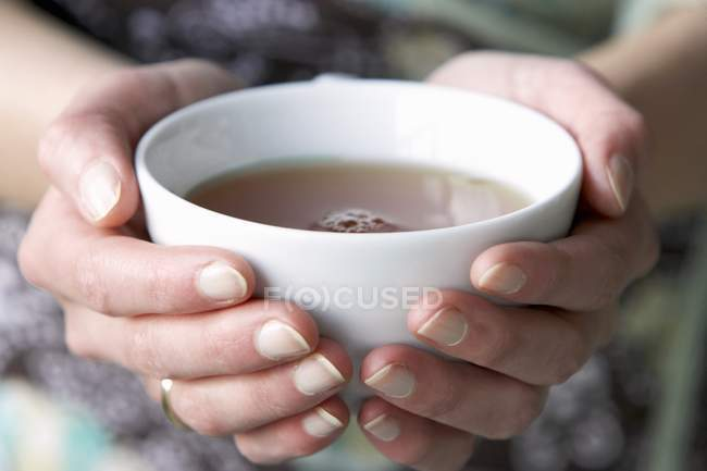 Mains tenant une tasse de thé — Photo de stock