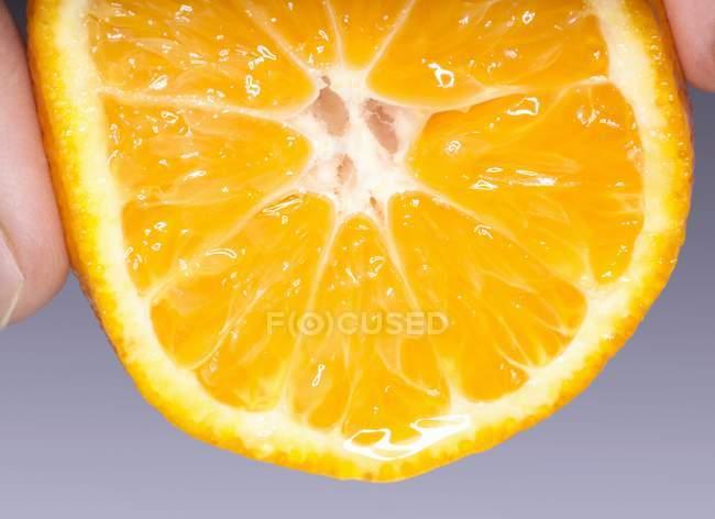 Hand squeezing mandarin orange half — Stock Photo