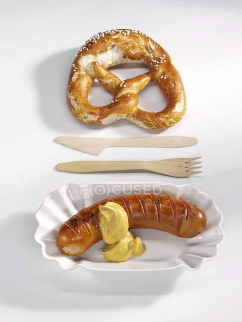 Червоний ковбаса з гірчицею і кренделі — стокове фото