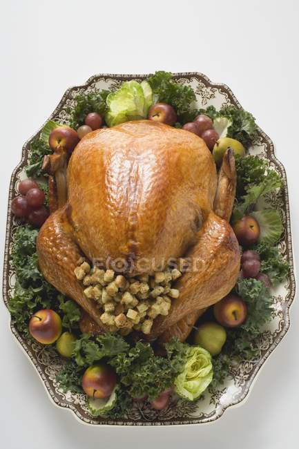 Stuffed turkey on platter with vegetables — Stock Photo