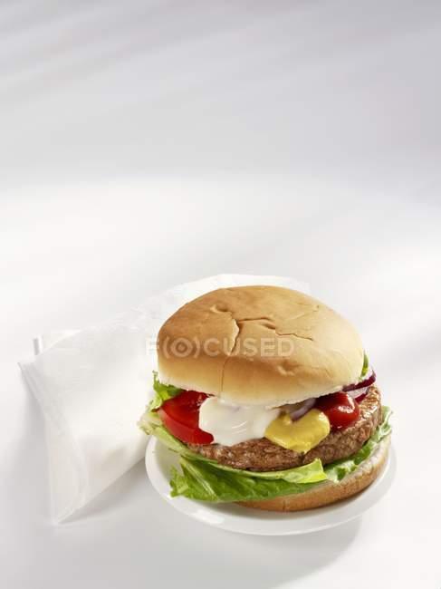 Vista de cerca de una hamburguesa con mostaza, ketchup y mayonesa - foto de stock